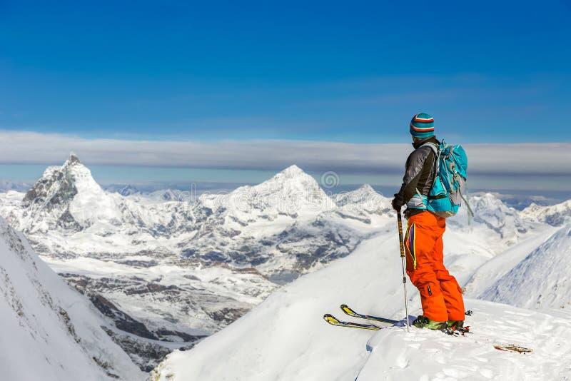 年轻运动人滑雪在一个晴天有美丽的景色  库存照片