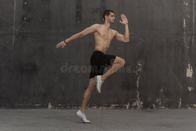年轻运动员人,赤裸躯干,运行对灰色墙壁  免版税库存图片