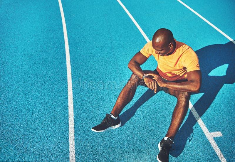 年轻运动员坐检查他的来回所需之时间的轨道 免版税库存图片