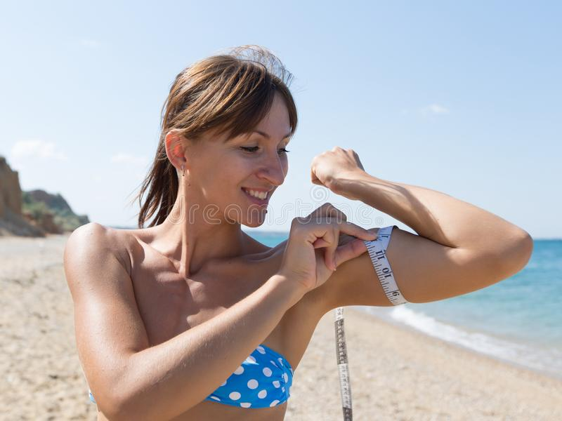 年轻运动员测量她的在海滨的二头肌 免版税库存照片