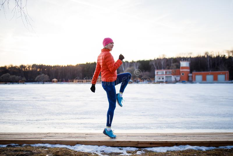年轻运动员金发碧眼的女人potrtait在早晨在冬天行使