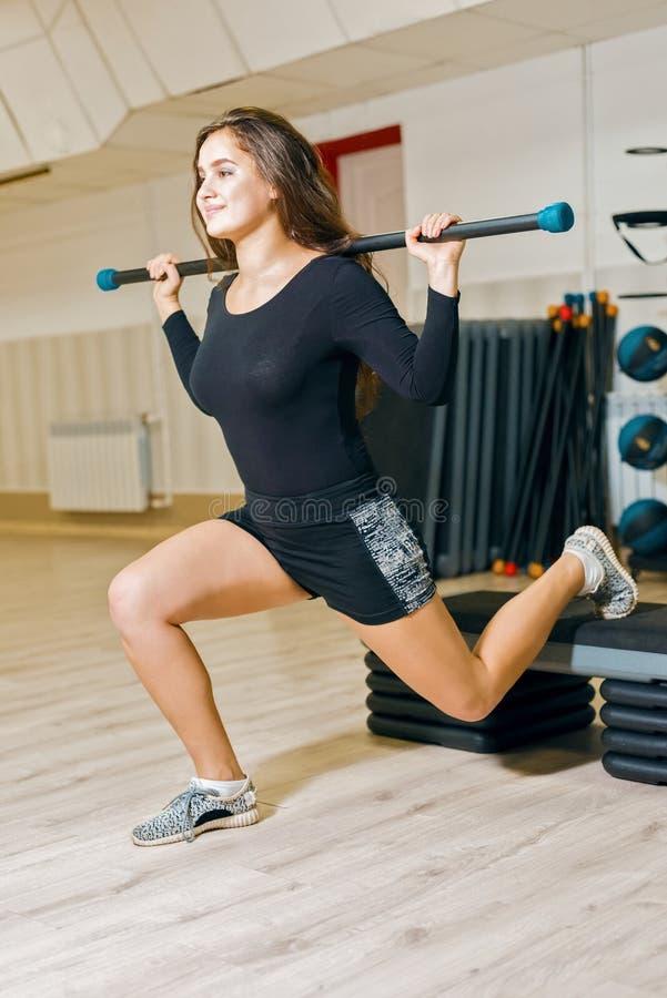 年轻运动女孩火车在健身屋子里 妇女蹲下用在平台的体操棍子步的 图库摄影