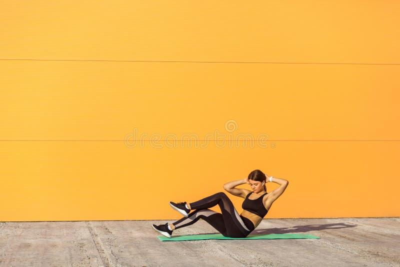年轻运动妇女实践,做十字形锻炼,自行车咬嚼摆在,制定出,佩带运动服,黑色裤子和 免版税图库摄影