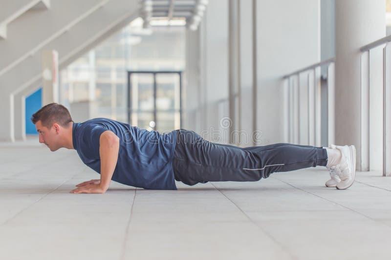 年轻运动的人在体育中心的做俯卧撑 库存照片