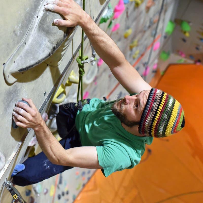 年轻运动的人bouldering在一个上升的大厅里的-室内运动 免版税图库摄影