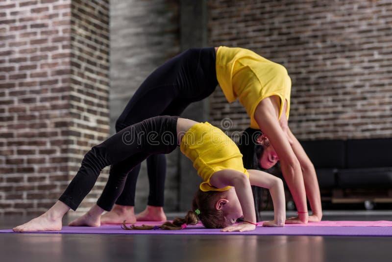 年轻运动的做母亲和的小女孩舒展一起站立在席子的螃蟹姿势的体操锻炼  库存照片