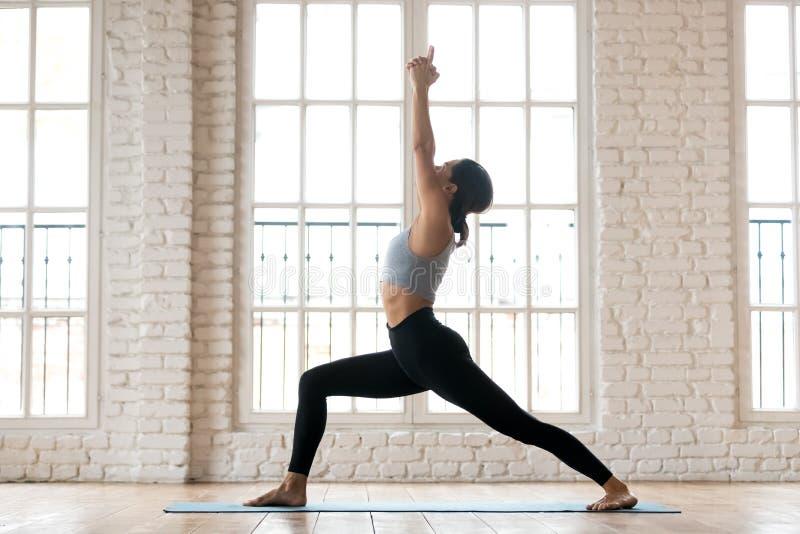 年轻运动的可爱的女子实践的瑜伽,做战士一 免版税库存照片