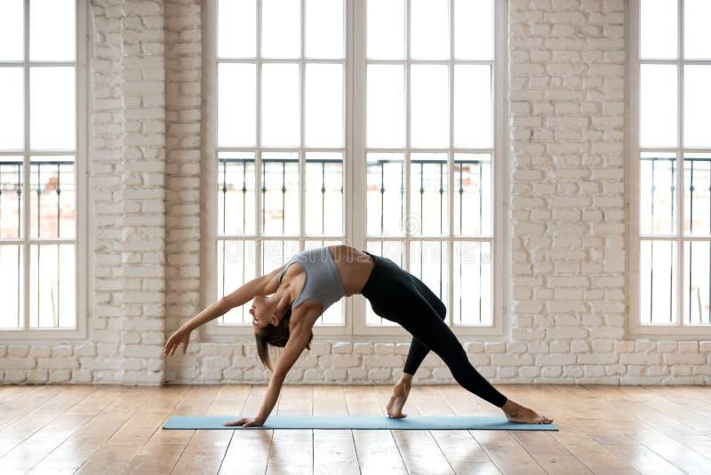 年轻运动的可爱的女子实践的瑜伽,做狂放的事 库存图片