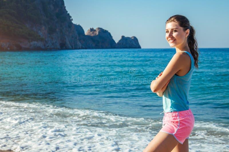 年轻运动的妇女有休息在海滩的一种锻炼以后 免版税图库摄影