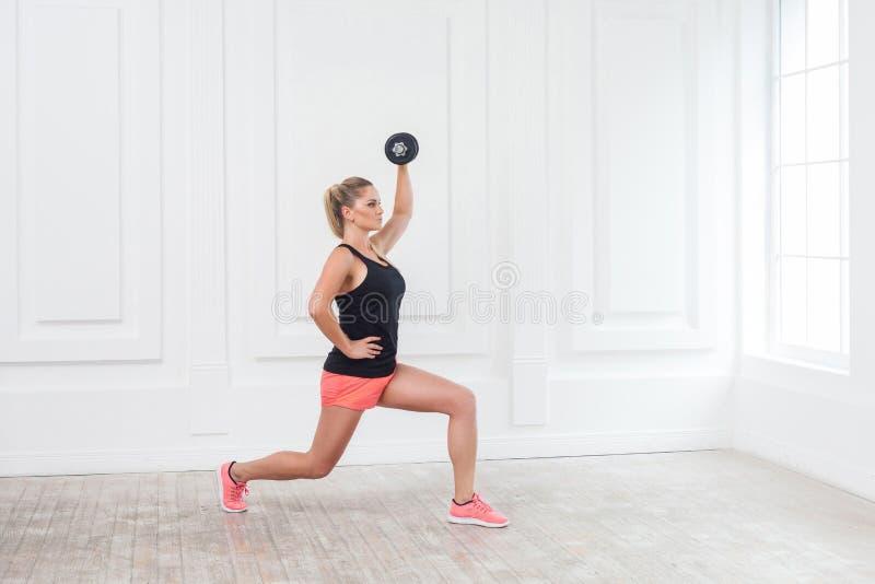 年轻运动美丽的爱好健美者妇女侧视图画象桃红色短裤的和黑顶面举行的dumbells在头顶上和做 库存照片