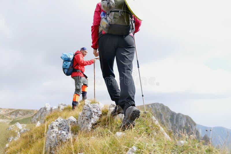 年轻远足者的腿特写镜头走在国家道路的 年轻夫妇足迹醒来 在远足鞋子的焦点 图库摄影