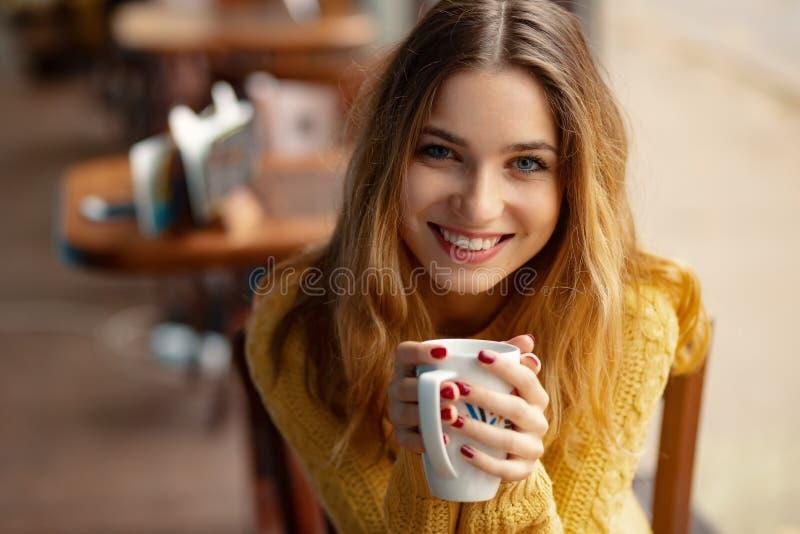 年轻迷人的妇女食用咖啡在咖啡馆 免版税库存图片