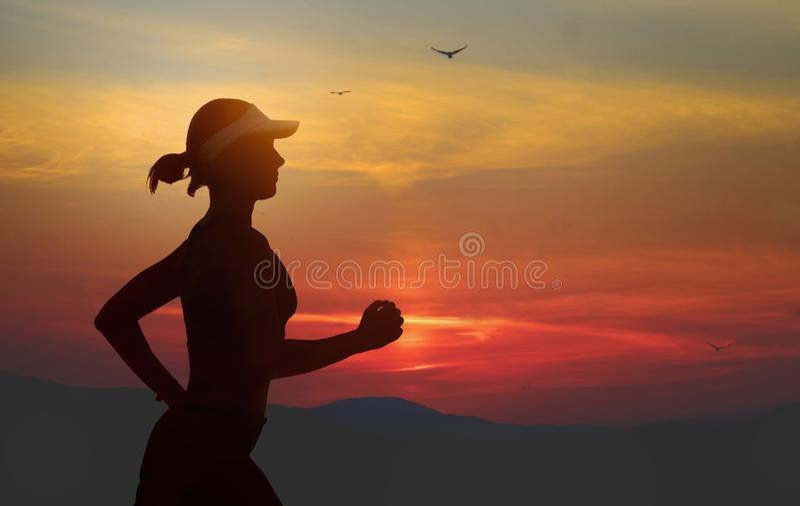 年轻适合和可爱的妇女美国盖帽训练在做连续健身锻炼的日落在美丽的橙色天空下  库存图片
