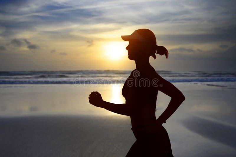 年轻适合和可爱的妇女美国盖帽训练在做连续健身锻炼的日落海滩在美丽的天空下  库存图片