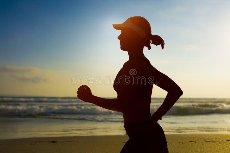 年轻适合和可爱的妇女美国盖帽训练在做连续健身锻炼的日落海滩在美丽的天空下  图库摄影
