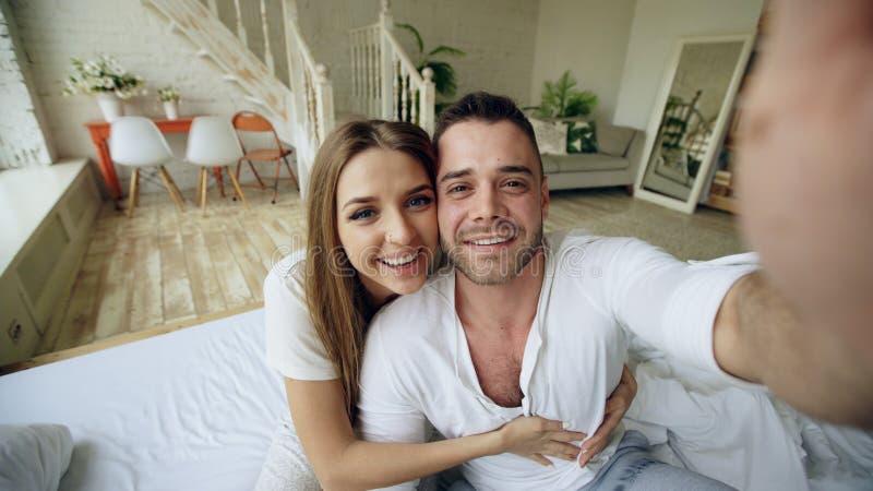年轻逗人喜爱和爱恋的夫妇有拿着片剂计算机和聊天对父母的录影闲谈在家坐在床 图库摄影