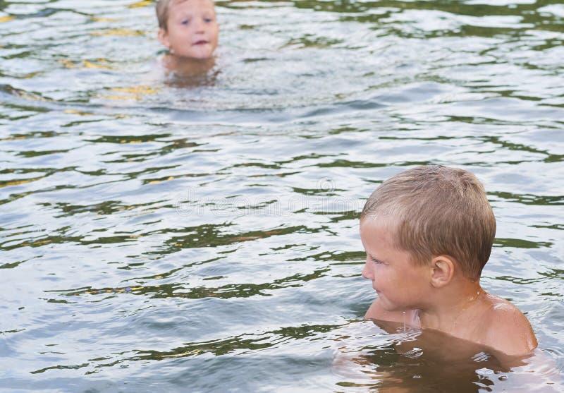 年轻逗人喜爱的使用在水中的男孩和他的弟弟在一个美丽的河或湖在一个晴朗的夏日 免版税库存照片