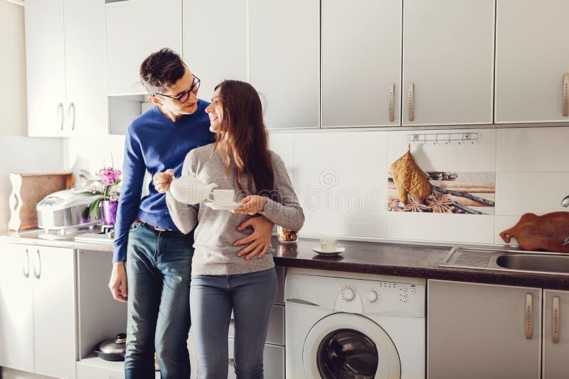 年轻逗人喜爱的夫妇拥抱的和饮用的茶在厨房里 库存图片