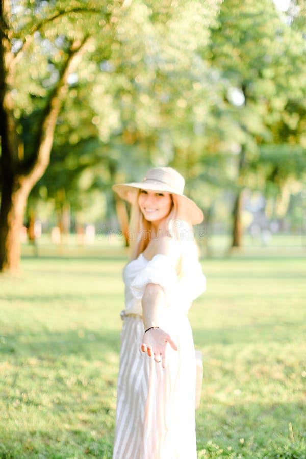 年轻逗人喜爱的女孩佩带的帽子和在手边站立在公园,焦点 库存照片