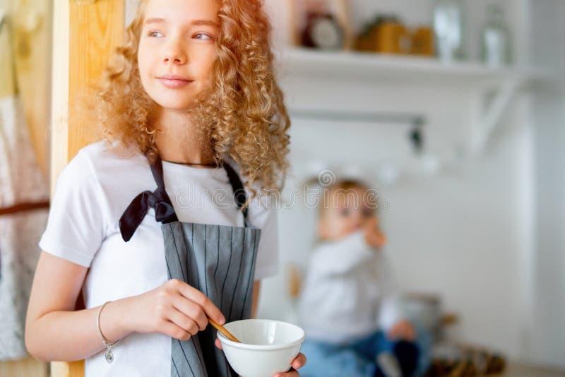 年轻逗人喜爱的女孩和她的小孩姐妹早餐为父母做准备 库存图片
