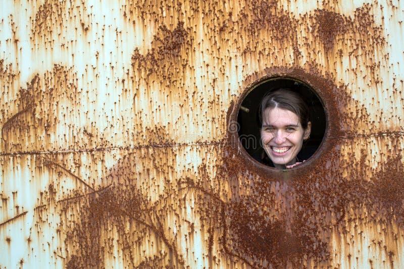 年轻逗人喜爱的妇女从窗口看生锈的工业对象 免版税库存照片