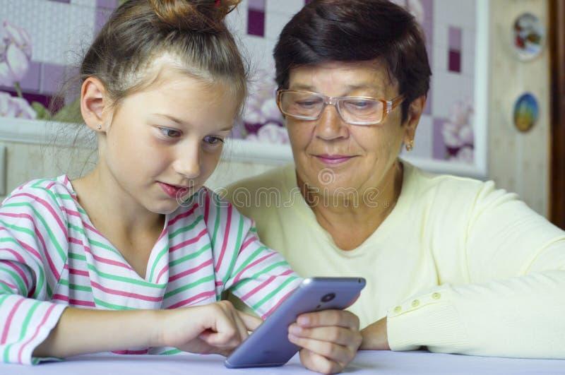 年轻逗人喜爱的孙女教的祖母如何在家使用智能手机 库存照片