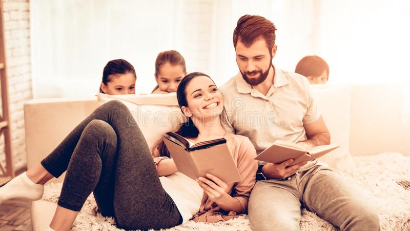 年轻逗人喜爱的父母看书,当孩子使用时 免版税库存图片