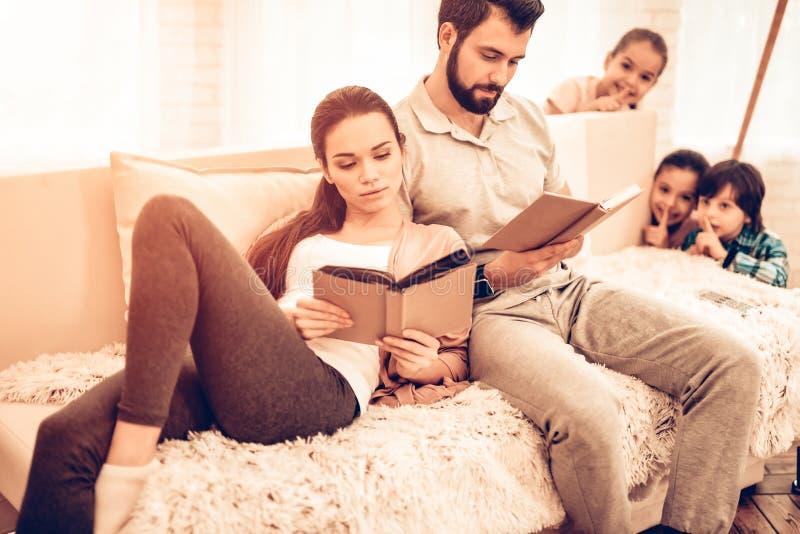 年轻逗人喜爱的父母看书,当孩子使用时 免版税库存照片