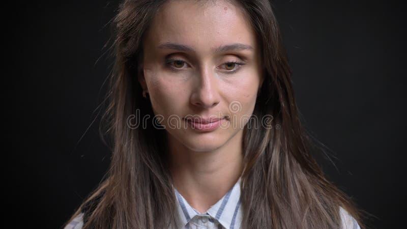 年轻逗人喜爱的白种人女性特写镜头画象有看下来在与隔绝的沉思的深色的头发的 免版税库存照片