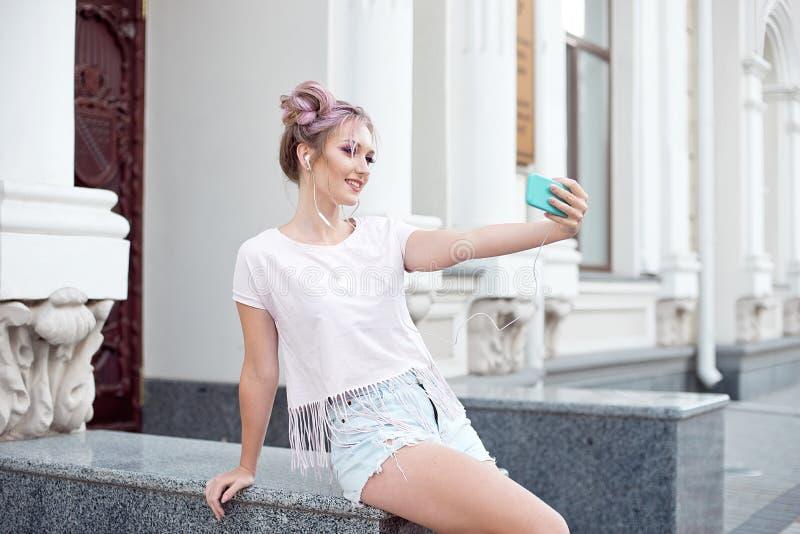 年轻逗人喜爱的金发碧眼的女人和明亮的桃红色嘴唇坐长凳,采取在她的智能手机的一selfie,在牛仔布短裤,桃红色T 库存图片