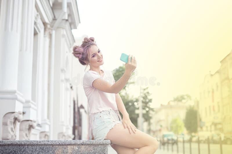 年轻逗人喜爱的金发碧眼的女人和明亮的桃红色嘴唇坐长凳,采取在她的智能手机的一selfie,在牛仔布短裤,桃红色T 免版税库存照片