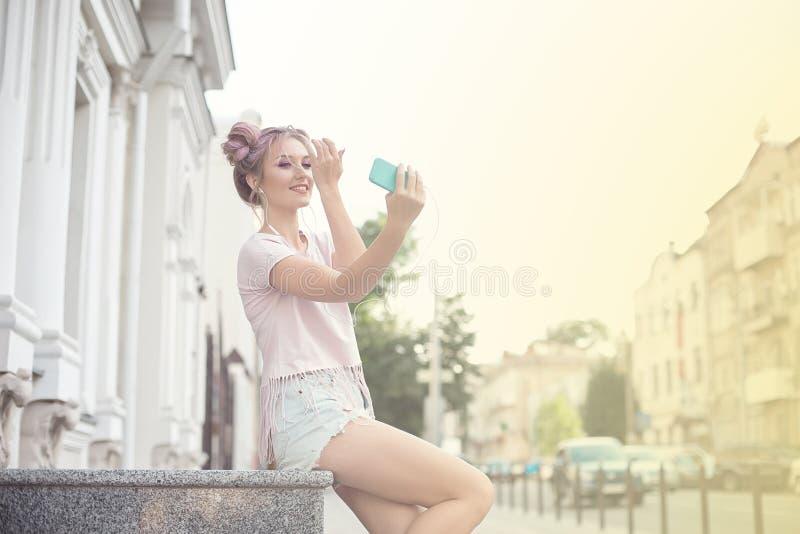 年轻逗人喜爱的金发碧眼的女人和明亮的桃红色嘴唇坐长凳,采取在她的智能手机的一selfie,在牛仔布短裤,桃红色T 免版税图库摄影