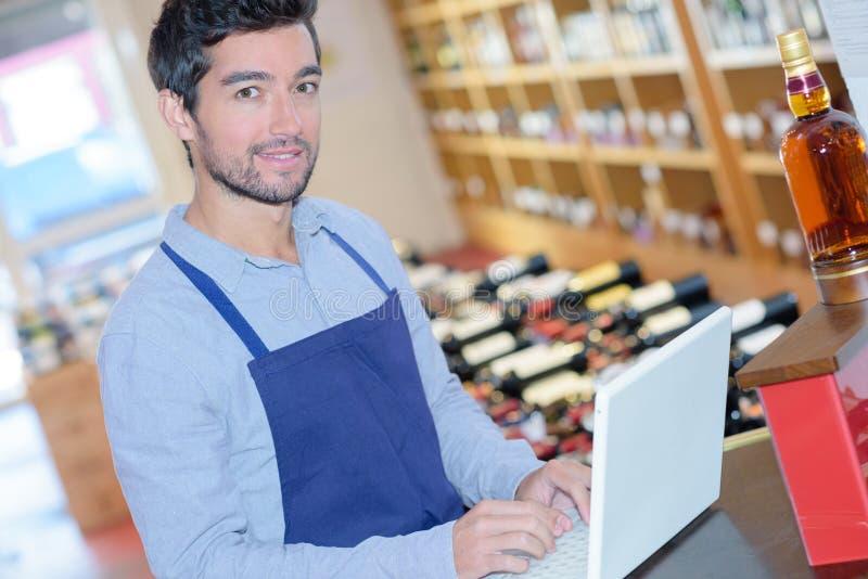 年轻酿酒商与膝上型计算机一起使用 免版税库存图片