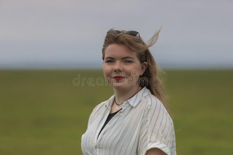 年轻金发碧眼的女人在草甸 免版税库存照片