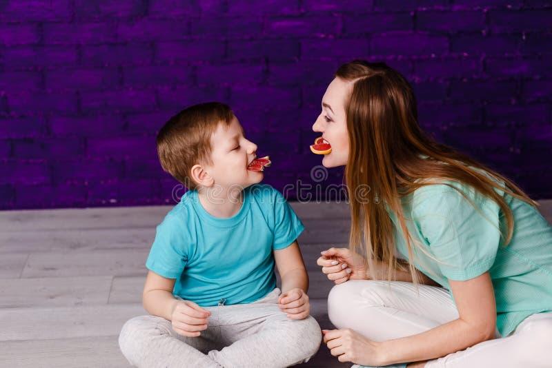 年轻长发母亲和七岁小孩获得乐趣 免版税库存图片