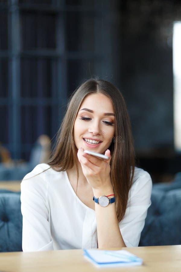 年轻长的头发夫人谈话由电话在餐馆 免版税图库摄影