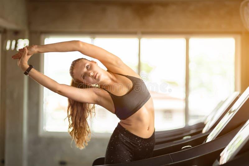 年轻长的白肤金发的在健身房的妇女有吸引力的健身锻炼锻炼 舒展肌肉和放松在锻炼以后的妇女 免版税库存照片
