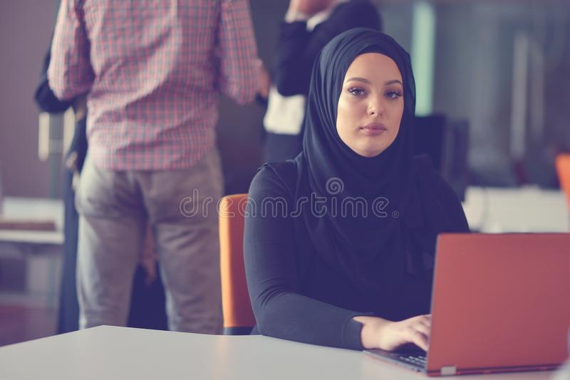 年轻阿拉伯女商人佩带的hijab,运作在她起始的办公室 变化,多种族概念 库存照片