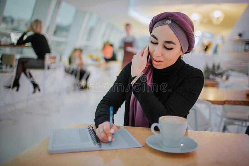 年轻阿拉伯女实业家在笔记本坐里面在桌上并且写 她在电话同时谈话 模型坐 免版税库存图片