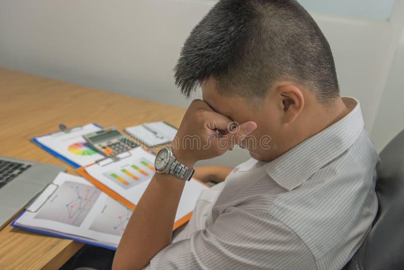 年轻雇员感受疲乏和沮丧在读许多销售报告以后 免版税库存图片