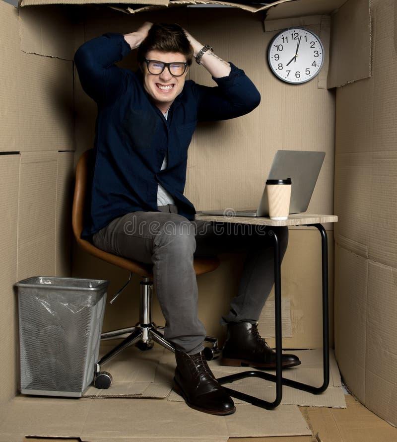 年轻雇员感觉在小纸室里面的愤怒 免版税库存图片
