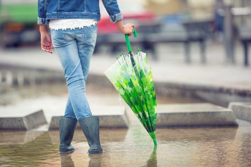 年轻青春期前的女孩站立与在水坑的一把伞在春天或夏天雨以后 免版税图库摄影