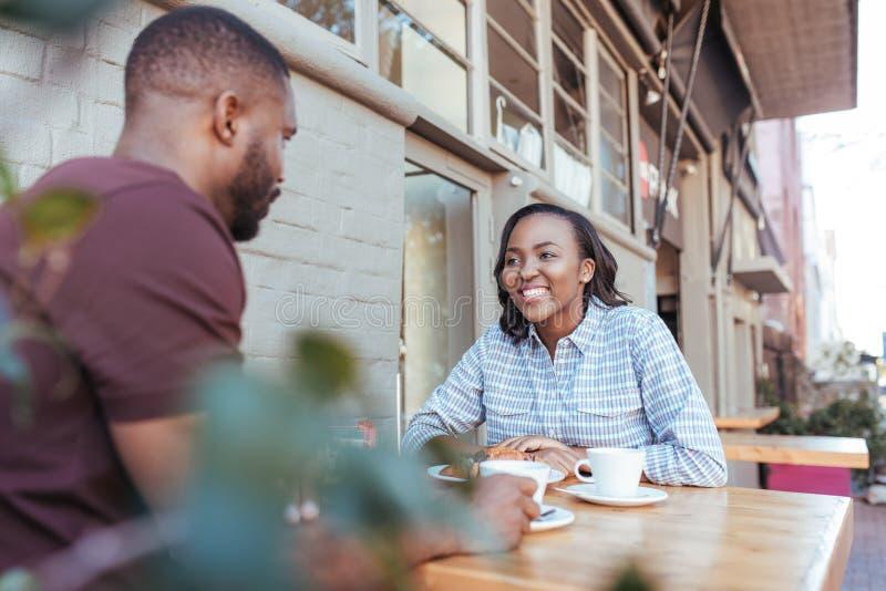 年轻非洲夫妇一起谈话在边路咖啡馆桌上 免版税库存照片
