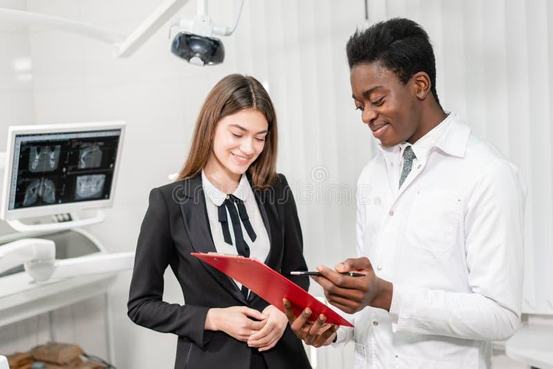 年轻非洲男性牙医提出一个诊断和纪录建议 牙齿诊所的妇女患者 ?? 免版税库存图片