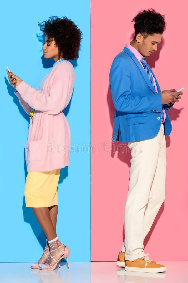年轻非洲amercian微笑的加上紧接站立在桃红色和蓝色的电话 库存图片