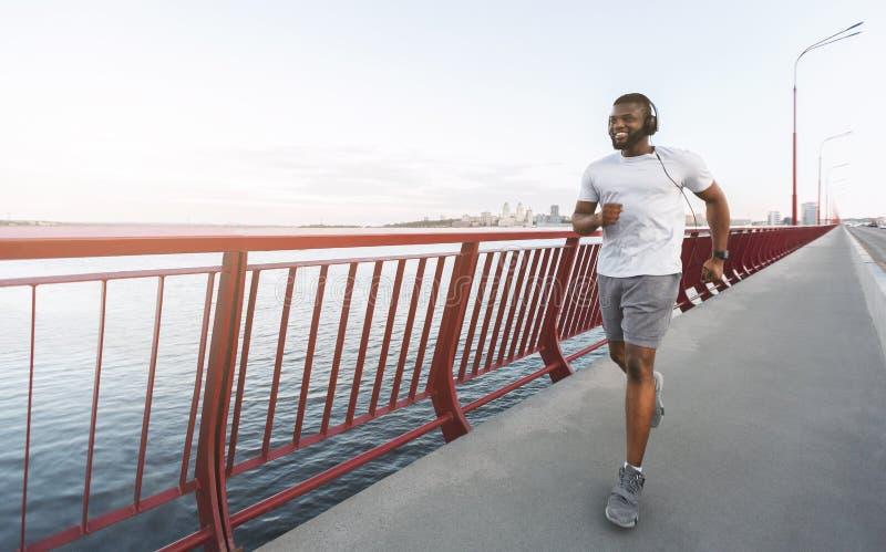 年轻非裔美国人的人享受跑步由桥梁 库存照片