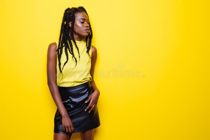 年轻非裔美国人的女孩秀丽画象有非洲的发型的 摆在黄色背景的女孩,看照相机,微笑 图库摄影