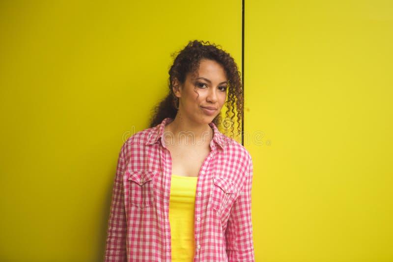 年轻非裔美国人的女孩秀丽画象有非洲的发型的 摆在黄色背景的女孩,看照相机 免版税图库摄影