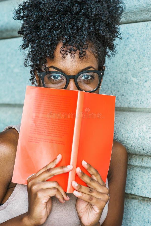 年轻非裔美国人的女性大学生看书outsi 免版税图库摄影