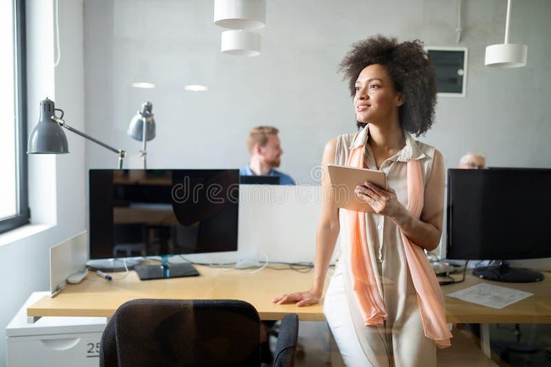 年轻非裔美国人的妇女与片剂一起使用在办公室 库存图片